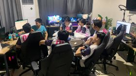 Blacklist International gathered around a table watching games on their computers