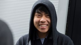 young boy smiling wearing a hoddie